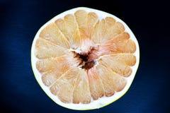 Текстурированный зрелый кусок цитрусовых фруктов помела на темной предпосылке конец вверх стоковые изображения rf