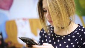 Текст азиатской девушки женщины печатая на smartphone который в черном случае силикона в форме кота видеоматериал