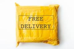 Текст БЕСПЛАТНОЙ ДОСТАВКИ на желтых пакете пакета или коробке груза с продуктом, свободная логистическая доставка и распределение стоковая фотография