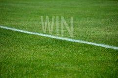 Текст выигрыша футбола на траве с белой майной Стоковая Фотография RF
