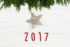 текст 2017 знаков на звезде рождества золотой на зеленых ветвях дерева o Стоковые Изображения