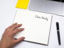 Текст конкретного исследования на тетради на столе работы Стоковые Изображения