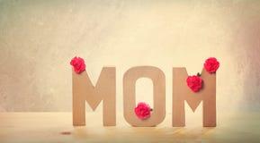 текст МАМЫ 3D с цветками гвоздики на таблице Стоковое Изображение RF
