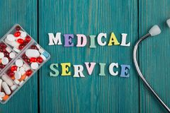 Текст & x22; Медицинское service& x22; покрашенных деревянных писем, стетоскопа и пилюлек Стоковое Фото