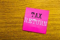 Текст объявления почерка показывая налоговую декларацию Концепция дела для учитывая возвращения денег написанного на бумаге липко стоковая фотография rf