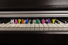 """Текст от с днем рождений красочных свечей """"на клавиатуре рояля стоковое фото rf"""