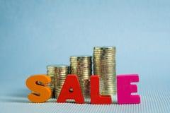 Текст продажи красочный деревянный с стогом монетки на голубом острословии предпосылки Стоковое фото RF