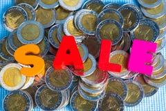 Текст продажи красочный деревянный с стогом монетки на голубом острословии предпосылки Стоковые Фотографии RF