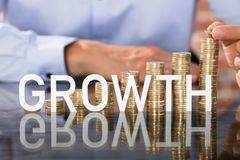 Текст роста перед стогом монеток Стоковое Изображение
