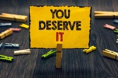 Текст сочинительства слова вы заслуживаете его Концепция дела для вознаграждения для хорошо сделанного что-то заслуживает стол Bl стоковые фото