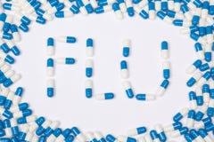 Текст слова гриппа сделанный голубых таблеток, пилюлек и капсул стоковые изображения