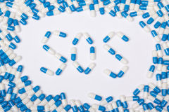 Текст слова Sos сделанный голубых таблеток, пилюлек и капсул стоковые изображения