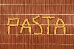 Текст формулируя Rotini Fusilli макаронных изделий на коричневом комплекте бамбука Стоковая Фотография