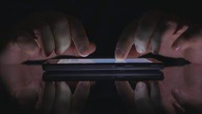 Текст человека используя экран касания сотового телефона в темном доступе в интернет доступа офиса стоковое изображение rf