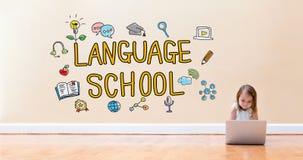 Текст языковой школы при маленькая девочка используя портативный компьютер стоковое изображение