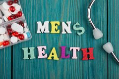 Текст & x22; Men& x27; health& x22 s; покрашенных деревянных писем, стетоскопа и пилюлек Стоковая Фотография