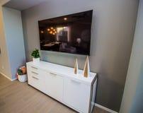 Телевидение плоского экрана над белым комодом стоковые изображения rf