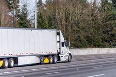 Тележка большого снаряжения белая semi транспортируя коммерчески груз в сухом трейлере фургона semi управляя на прямой широкой до стоковая фотография rf
