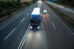 Тележка и автомобили быстро проходя на шоссе в вечере Стоковые Изображения