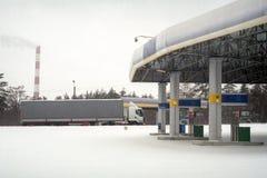 Тележка проходит бензоколонкой после обильные снежности Стоковая Фотография