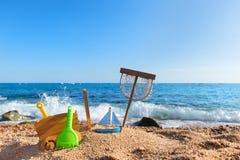 Тележка руки и другие винтажные игрушки на пляже стоковая фотография rf