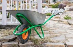 Тележка руки с колесом для стоек сбора мусора, конструкции и домочадца на предпосылке выхоленного колодца и ennob стоковые фото