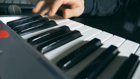 Тележка сняла мужских рук музыканта играя на синтезаторе на ядровой студии звукозаписи Запев игр оружий людей музыки сток-видео