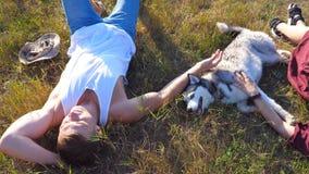 Тележка сняла счастливых пар лежа на зеленой траве на поле и ласкает их собаку сибирской лайки на солнечном дне Молодые пары внут сток-видео