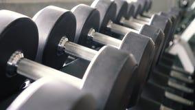 Тележка снятая гантелей и штанги гребут в современном спортзале спортивного клуба сток-видео