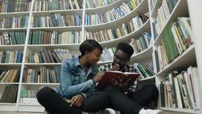 Тележка снятая молодого африканских мужчины и студенток сидя на поле около полок книг пока книга чтения внутри акции видеоматериалы