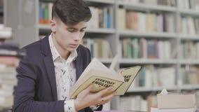 Тележка снятая молодого исследования студента крепко в библиотеке Мужской студент университета проводя исследование исследование  сток-видео