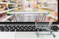 Тележка супермаркета на портативном компьютере с гастрономом нерезкости Стоковые Изображения