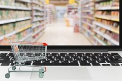 Тележка супермаркета на портативном компьютере с гастрономом нерезкости Стоковое фото RF