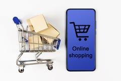 Тележка супермаркета с коробками и смартфон на белой предпосылке прочешите покупка руки фокуса dof он-лайн отмелая очень стоковые фото