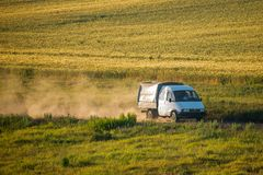 Тележка управляет на грязной улице и завихряет облако пыли среди полей Стоковое фото RF
