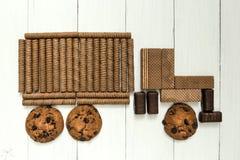 Тележка шоколада принесла помадки Помадки шоколада, крены вафли шоколада, печенья на деревянной белой таблице стоковая фотография rf