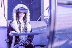 Телефона брюнета шлемофона виртуальной реальности женщины стороны девушки пинка VR зима мебели неба пурпурного голубого футуристи стоковые фото