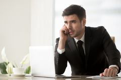 Телефонный звонок бизнесмена отвечая на столе в офисе Стоковые Изображения