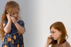 телефоны 2 девушок клетки стоковая фотография