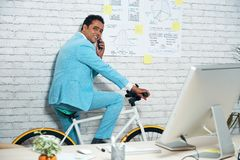 Телефон бизнесмена отвечая на велосипеде Стоковые Изображения