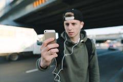 Телефон в фокусе на предпосылке запачканного молодого человека в наушниках и городском ландшафте Студент переключает музыку на th стоковое фото rf