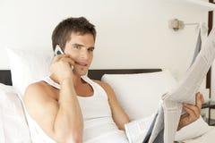 телефон газеты кровати Стоковое Изображение
