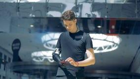Телефон держится простетической рукой мужчины подростковый Будущая принципиальная схема