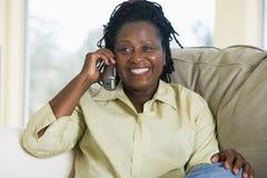 телефон живущей комнаты сидя используя женщину Стоковые Изображения RF