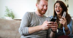 Телефон жизнерадостных пар смеясь над наблюдая умный Стоковое Изображение RF