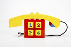Телефон игрушки младенца иллюстрирует обслуживание клиента на вебсайте или любом телефонном номере обслуживаний Телефон для формы Стоковое фото RF
