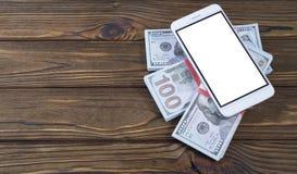 Телефон и деньги концепции на предпосылке дерева Идея дела, устройства, применения smartphone Стоковое Изображение