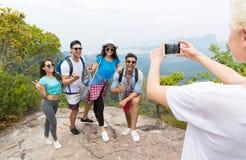 Телефон клетки умный принимая фото жизнерадостной туристской группы с рюкзаком над ландшафтом от верхней части горы, представлять стоковые фотографии rf
