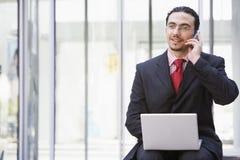 телефон компьтер-книжки бизнесмена передвижной внешний используя Стоковое фото RF