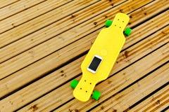 Телефон лежит на желтом пластиковом longboard, которое расположено на деревянном настиле Взгляд сверху стоковая фотография rf
